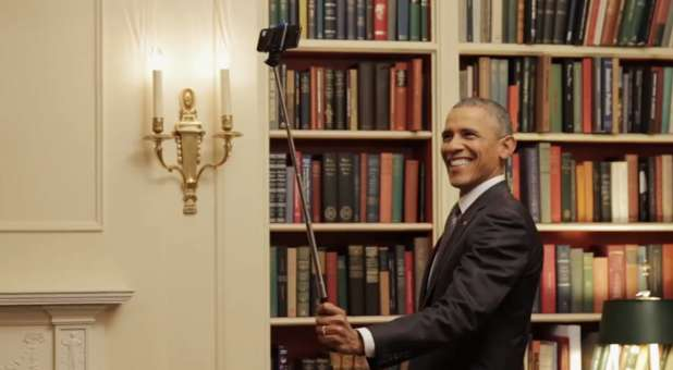 U.S. President Barack Obama taking a selfie with a selfie stick.