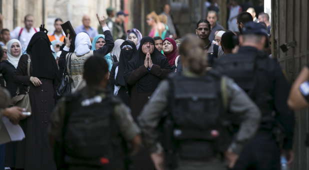 Muslim women shouts slogans as they protest in front of Israeli border police officers in Jerusalem's Old City, Sept. 15, 2015. Violence in the city of Jerusalem has increased, prompting some groups to form prayer shields over the city.