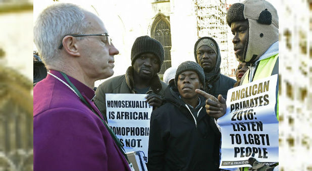 Archbishop of Canterbury Justin Welby, left, speaks with protesters on the grounds of Canterbury Cathedral in Canterbury, England.