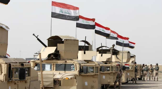 Iraqi security forces ride in vehicles travelling to Mosul to fight against militants of Islamic State.