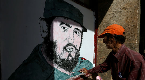 A local artist paints a portrait of Fidel Castro in front of a shop in downtown Havana following the announcement of the death of the Cuban revolutionary leader