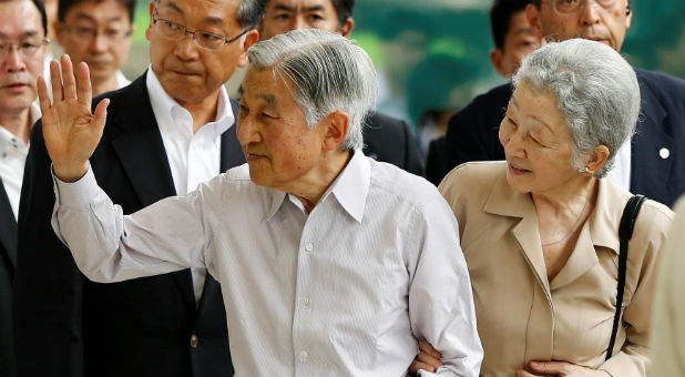 Japan's Emperor Akihito (L), flanked by Empress Michiko, waves to well-wishers as they board a Shinkansen bullet train to depart to their imperial summer villa in Nasu, at Tokyo station in Tokyo, Japan