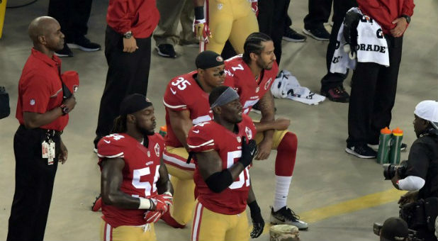 San Francisco 49ers quarterback Colin Kaepernick (7) and free safety Eric Reid (35) kneel during the playing of the national anthem before a NFL game against the Los Angeles Rams at Levi's Stadium