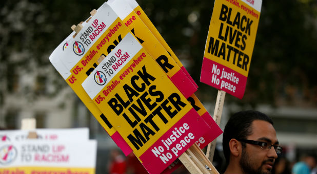 "A supporter of the UK branch of ""Black Lives Matter"" hands out placards at the start of a demonstration in London, Britain"