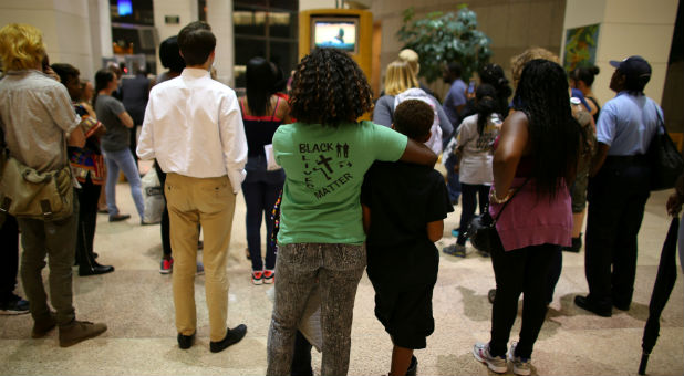 A mother and her children stand among an overflow crowd as they watch and listen outside city council chambers in Charlotte