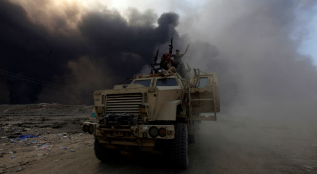 Iraqi army personnel ride on a military vehicle in Qayyarah, during an operation to attack Islamic State militants in Mosul, Iraq, Oct. 19, 2016.