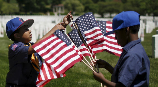 Members of the Boy Scouts of America organize U.S. flags to be placed at graves at Cypress Hills National Cemetery in Brooklyn, New York