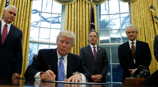 U.S. President Donald Trump, watched by (L-R) Vice President Mike Pence, White House Chief of Staff Reince Priebus, head of the White House Trade Council Peter Navarro and senior adviser Jared Kushner, signs an executive order that places a hiring freeze on non-military federal workers in the Oval Office of the White House in Washington