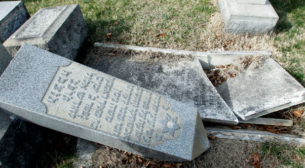 A headstone, pushed off its base by vandals, lays on the ground near a smashed tomb in the Mount Carmel Cemetery, a Jewish cemetery, in Philadelphia, Pennsylvania. About 100 headstones were knocked over, police said, in an incident that apparently took place after dark on Feb. 25.