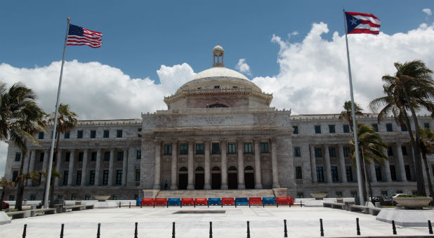 The flags of the U.S. and Puerto Rico fly outside the Capitol building in San Juan, Puerto Rico.