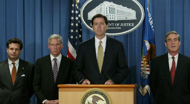 Deputy U.S. Attorney General James B. Comey, accompanied by Assistant Attorney General Christopher A. Wray (L) of the Criminal Division, IRS Commissioner Mark Everson (2nd L) and FBI Director Robert Mueller, speaks during a news conference in the Justice Department in Washington, July 8, 2004.