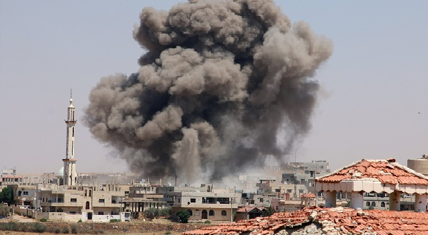 Smoke rises after airstrikes on a rebel-held part of the southern city of Deraa, Syria.