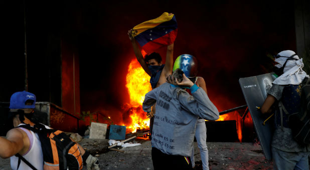 Protesters are seen next to a fire burning at the entrance of a building housing the magistracy of the Supreme Court of Justice and a bank branch, during a rally against Venezuela's President Nicolas Maduro, in Caracas, Venezuela.