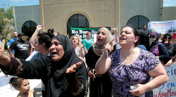 A group of women react as they talk about family members seized on Sunday by Immigration and Customs Enforcement agents during a rally outside the Mother of God Catholic Chaldean church in Southfield, Michigan.