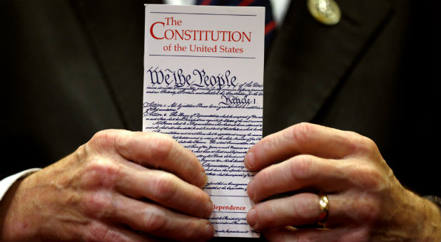 A member of Congress holds a copy of the U.S. Constitution.
