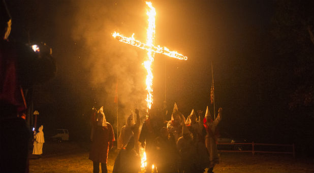 Members of the Rebel Brigade Knights and the Nordic Order Knights, groups that both claim affiliation with the Ku Klux Klan, gather for a group photograph in front of a lit cross after a cross lighting ceremony at a private residence in Henry County, Virginia, Oct.11, 2014.