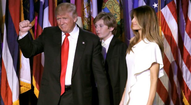 U.S. President Donald Trump gestures as the takes the stage with his wife Melania and his son Baron