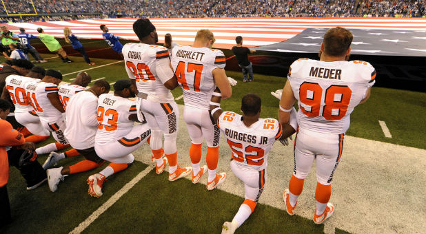 The Cleveland Browns team stands and kneel during the National Anthem before the start of their game against the Indianapolis Colts.