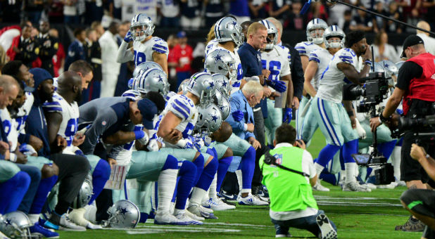 The Dallas Cowboys players, coaches staff and owner Jerry Jones take a knee prior to the National Anthem.
