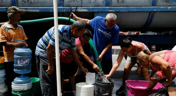 People queue to fill containers with water from a tank truck at an area hit by Hurricane Maria.