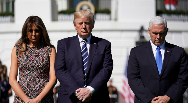 The first lady, president and vice-president observe a moment of silence.