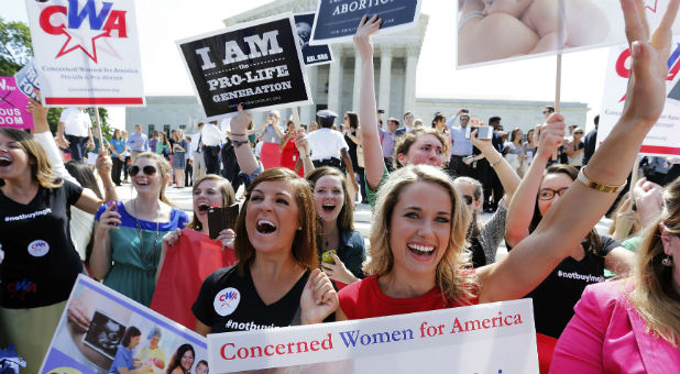 Pro-life demonstrators cheer as the ruling for Hobby Lobby was announced outside the U.S. Supreme Court in Washington June 30, 2014.