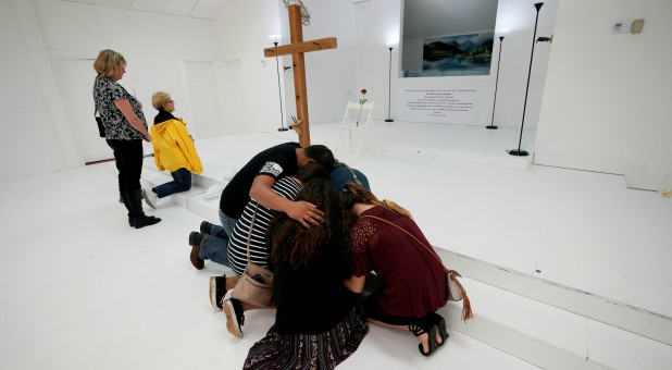 People pray in the First Baptist Church of Sutherland Springs where 26 people were killed in a shooting attack last week, as the church was opened to the public as a memorial to those killed.