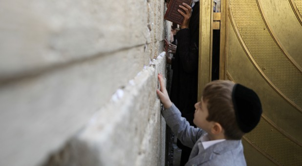 A child touches the Western Wall, Judaism's holiest prayer site, as a woman prays in the women's section of the site.
