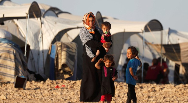 A woman and her children stand outside their tent at a refugee camp for people displaced by fighting between the Syrian Democratic Forces and Islamic State militants.