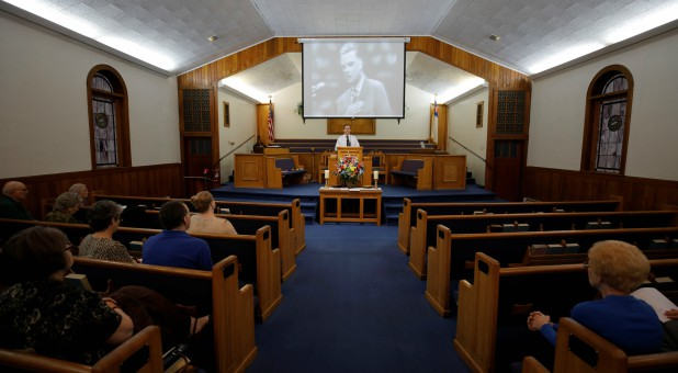 Reverend Bobby Shehan preaches under a projected image of evangelist Billy Graham.