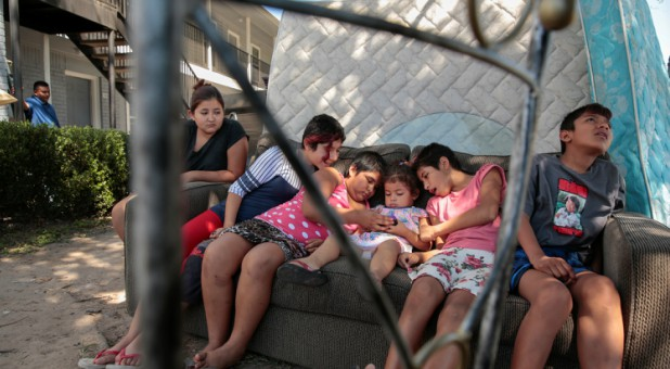 Children watch cartoons outside of their north Houston apartment in the aftermath of Hurricane Harvey in Houston, Texas.
