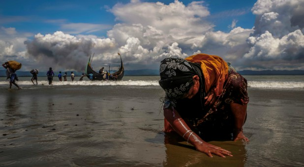 An exhausted Rohingya refugee woman touches the shore after crossing the Bangladesh-Myanmar border.