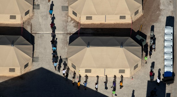 Immigrant children are led by staff in single file between tents at a detention facility next to the Mexican border.