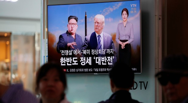 People watch a TV broadcasting a news report on the upcoming summit between the U.S. and North Korea.