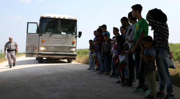 Immigrants who turned themselves in to border patrol agents after illegally crossing the border from Mexico into the U.S. wait to be transported for processing in the Rio Grande Valley sector.