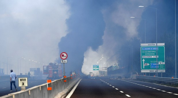 Firefighters work on the motorway after an accident caused a large explosion and fire at Borgo Panigale.