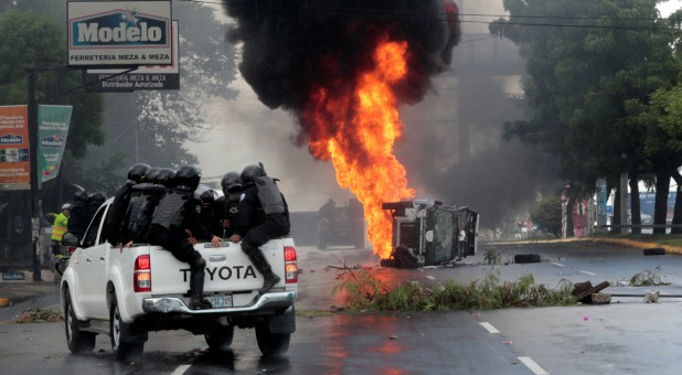 Riot police officers travel past a burning police car during a protest against Nicaraguan President Daniel Ortega's government in Managua, Nicaragua.