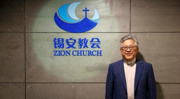 "The head pastor of the Zion church in Beijing, Jin Mingri. poses for picures in the lobby of the unofficial Protestant ""house"" church in Beijing, China."