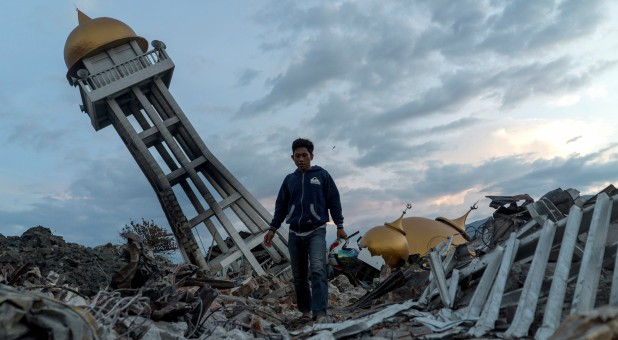 A resident walks at an area hit by the earthquake and tsunami in Palu, Central Sulawesi, Indonesia.
