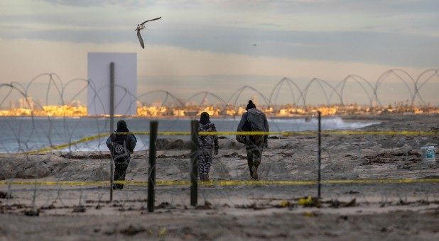 A migrant woman and two boys, part of a caravan of thousands from Central America trying to reach the United States, walk behind concertina wire on a beach in San Diego County after crossing illegally from Mexico to the U.S.