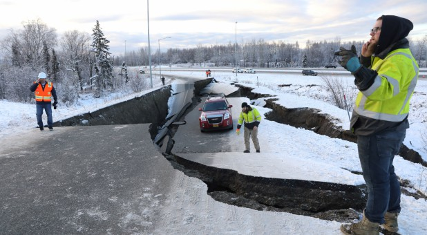 A stranded vehicle lies on a collapsed roadway near the airport after an earthquake in Anchorage, Alaska.