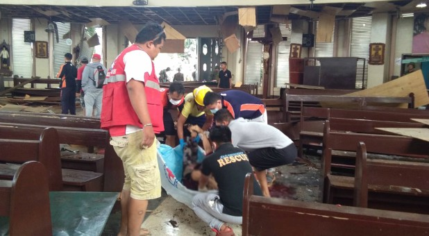 Members of the Philippine Red Cross attend to a casualty inside a church after a bombing attack in Jolo, Philippines.