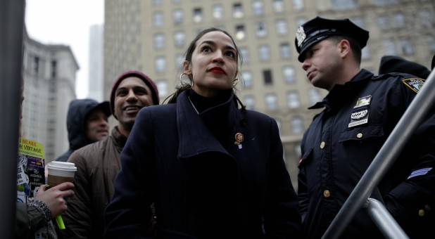 Representative Alexandria Ocasio-Cortez looks on as she awaits to be introduced to the crowd of supporters during the Women's March NYC.