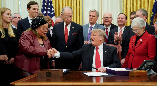 U.S. President Donald Trump shakes hands with Alveda King.