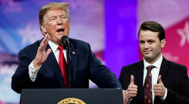 U.S. President Donald Trump speaks as Hayden Williams, member of the Leadership Institute, stands behind him at the Conservative Political Action Conference (CPAC) annual meeting.