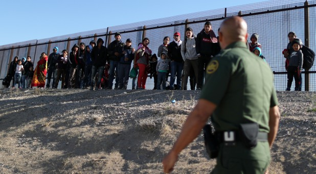 A group of Central American migrants surrenders to U.S. Border Patrol Agent Jose Martinez south of the U.S.-Mexico border fence in El Paso, Texas.