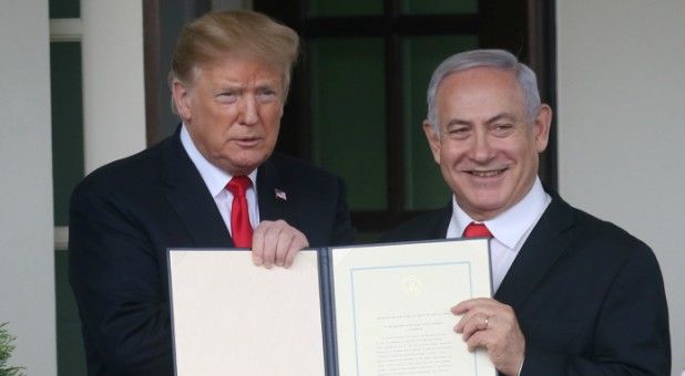 U.S. President Donald Trump and Israel's Prime Minister Benjamin Netanyahu hold up a proclamation recognizing Israel's sovereignty over the Golan Heights.