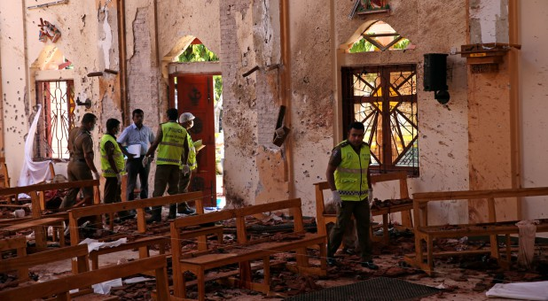 Police officers work at the scene at St. Sebastian Catholic Church, after bomb blasts ripped through churches and luxury hotels on Easter, in Negombo, Sri Lanka.