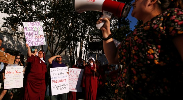 Pro-choice supporters protest in front of the Alabama State House as Alabama state Senate votes on the strictest anti-abortion bill in the United States.