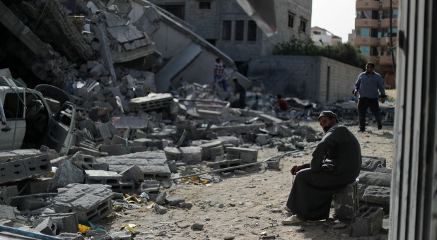 A man sits on debris near a building that was destroyed by Israeli air strikes, in Gaza City.